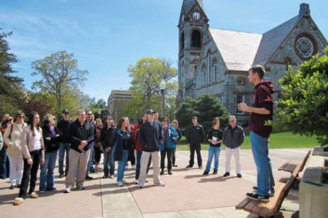 A group of students face a tour guide with a college building in the background.